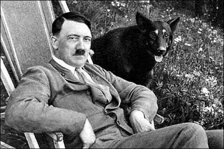 IN HIS HOURS OF EASE THE FÜHRER IN THE GARDEN, WITH ONE OF HIS PEDIGREE ALSATIANS BESIDE HIM.
